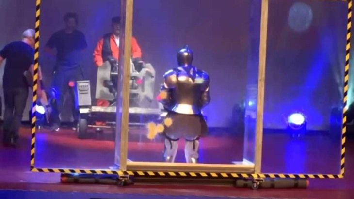 Audience member being shot with paint-balls while wearing a suit of armour at the Mythbusters behind the myths live show.